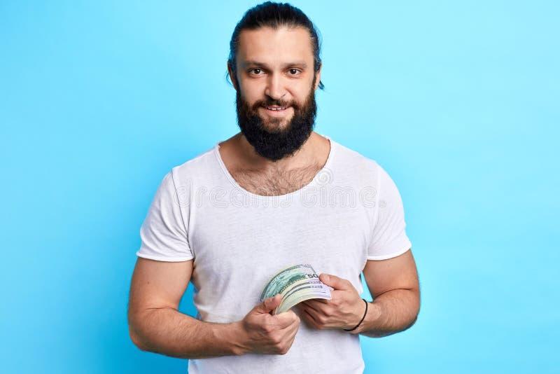 O retrato do homem novo alegre ganha o dinheiro na rede do th foto de stock royalty free
