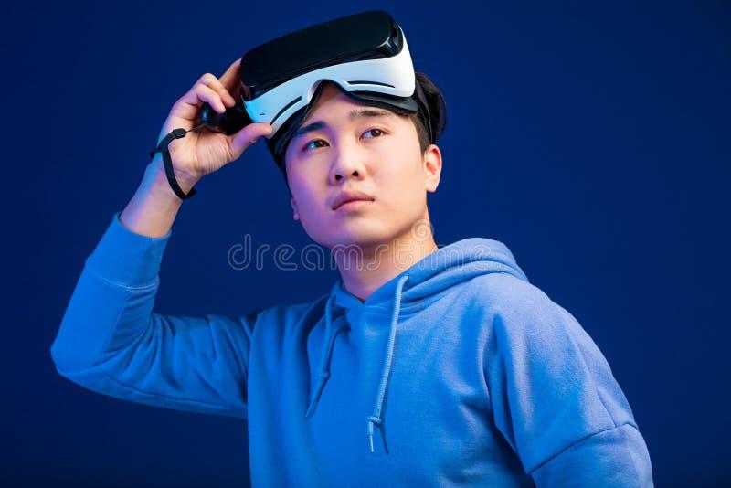O retrato do homem novo asiático decola seus vidros da realidade virtual de sua cabeça imagem de stock royalty free