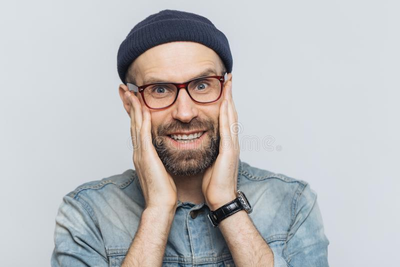 O retrato do homem novo atrativo com barba e o bigode grossos olha com expressão deleitada, tem os dentes perfeitos brancos, pose foto de stock