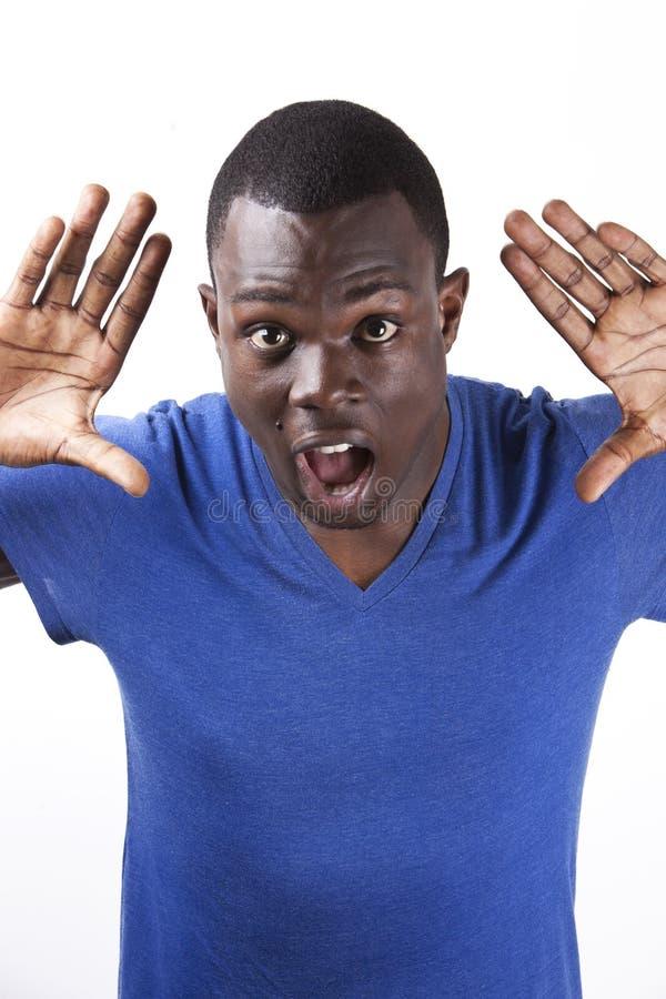 O retrato do homem novo chocado com palmas abre a posição contra o fundo branco fotos de stock