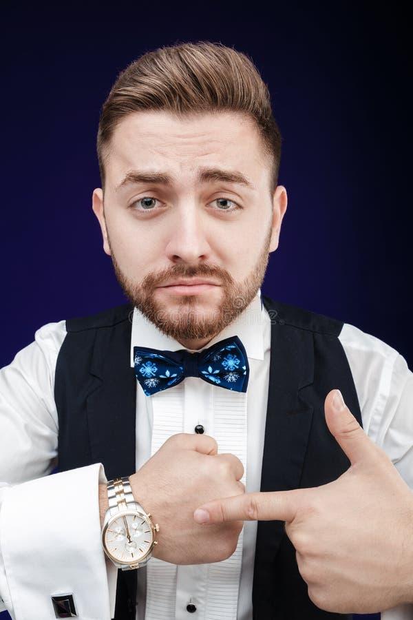 O retrato do homem novo com barba mostra ao relógio no backgro escuro fotografia de stock royalty free