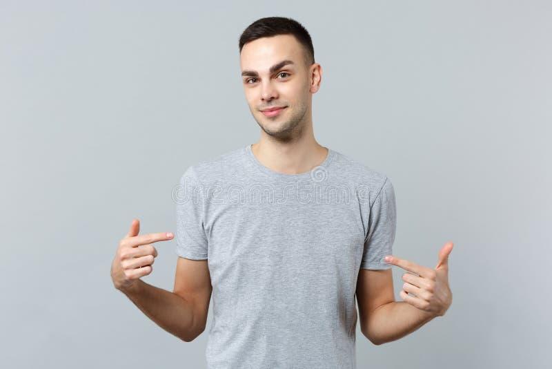 O retrato do homem novo considerável de sorriso na roupa ocasional que aponta os indicadores nsi mesmo isolou-se na parede cinzen fotografia de stock