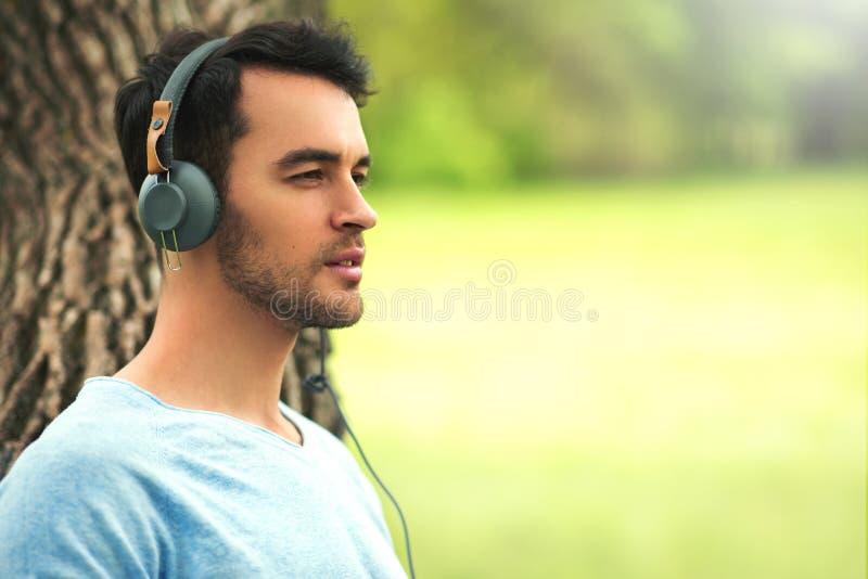 O retrato do homem novo de sonho bonito com fones de ouvido, escuta música na árvore imagem de stock
