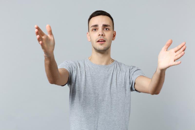 O retrato do homem novo desagradado na roupa ocasional está com as mãos outstretching de espalhamento isoladas na parede cinzenta foto de stock