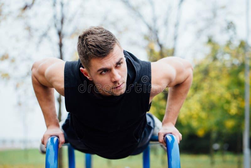 O retrato do homem novo muscular focalizado no exercício preto veste fazer mergulhos em barras paralelas foto de stock royalty free