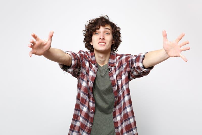 O retrato do homem novo surpreendido de defesa na roupa ocasional está com as mãos outstretching de espalhamento isoladas no bran foto de stock