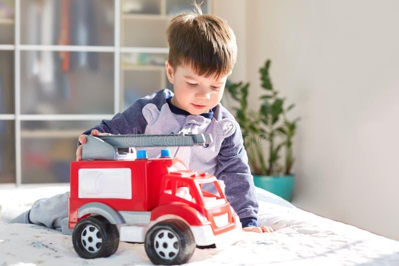 O retrato do homem pequeno com olhar atrativo, jogos com o automóvel vermelho do brinquedo, senta-se na cama, passa o tempo livre fotos de stock