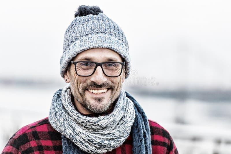 O retrato do homem urbano feliz no inverno fez malha o desgaste Retrato do homem nos vidros e lenço e chapéu branco-azuis feitos  fotografia de stock