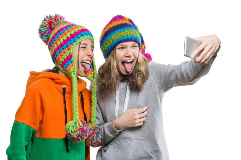 O retrato do inverno de duas amigas adolescentes bonitas felizes nos chapéus feitos malha que têm o divertimento com telefone cel imagens de stock royalty free