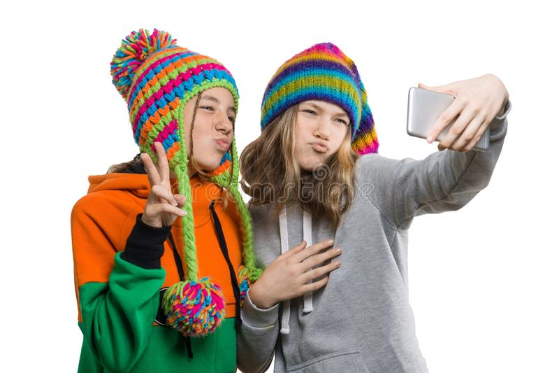 O retrato do inverno de duas amigas adolescentes bonitas felizes nos chapéus feitos malha que têm o divertimento com telefone cel fotos de stock