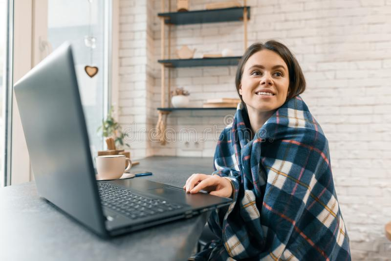 O retrato do inverno do outono da mulher de sorriso nova com laptop e xícara de café na cafetaria, menina travou wi cobertos frio fotografia de stock