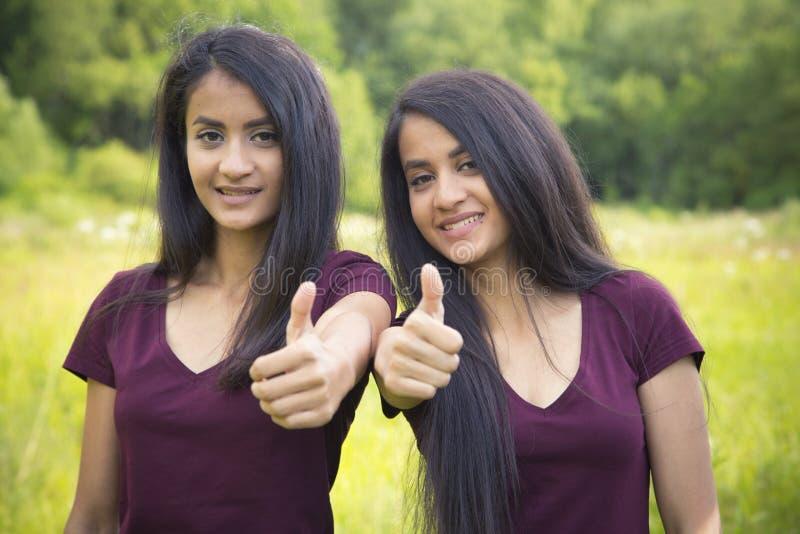 O retrato do irmãs felizes junta mostrar os polegares acima fotos de stock