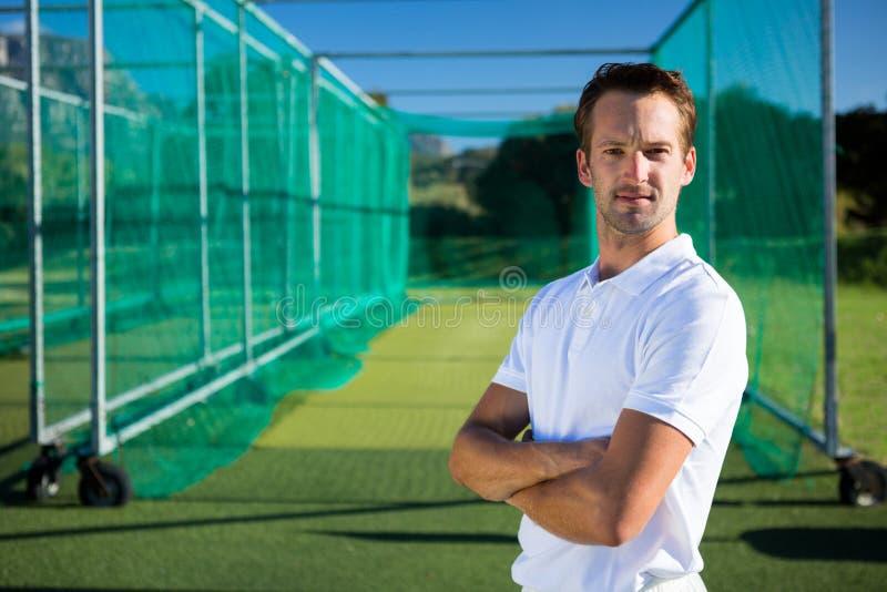 O retrato do jogador de cricket novo com braços cruzou a posição no campo fotos de stock royalty free