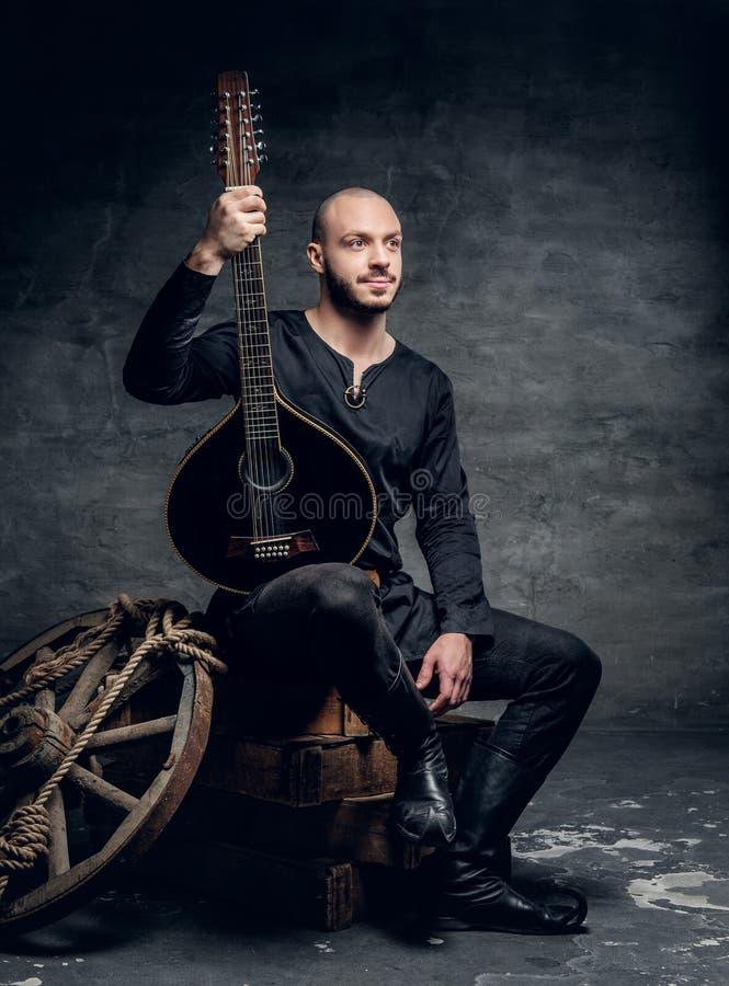 O retrato do músico popular tradicional vestido na roupa celta do vintage senta-se em uma caixa de madeira e guarda-se o bandolim imagens de stock