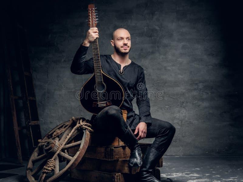 O retrato do músico popular tradicional vestido na roupa celta do vintage senta-se em uma caixa de madeira e guarda-se o bandolim imagem de stock royalty free