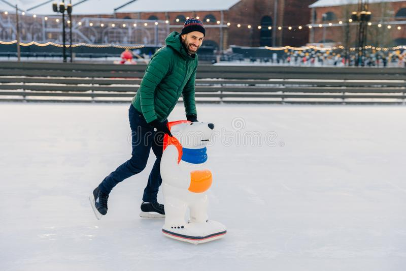 O retrato do meio considerável contente envelheceu os patins masculinos em wi da pista de gelo foto de stock