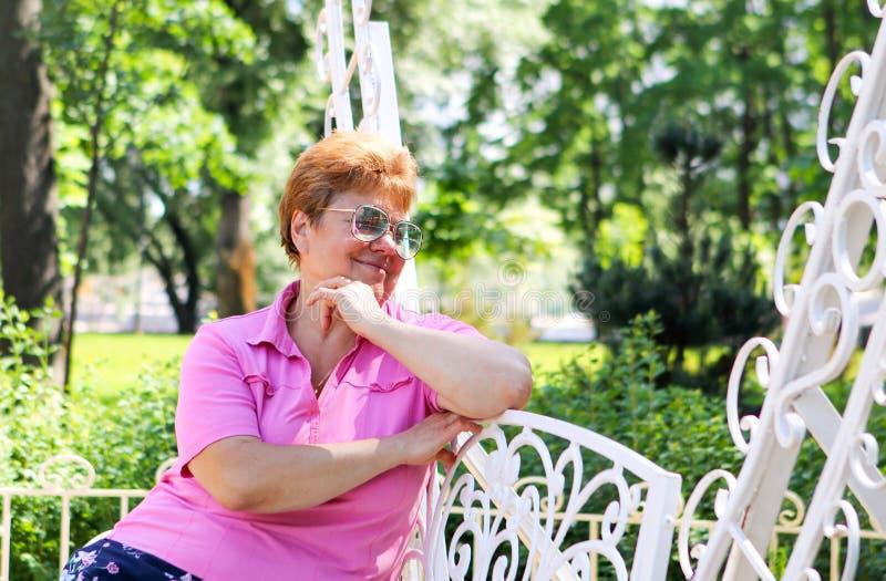 O retrato do meio de sorriso bonito envelheceu a mulher adulta que senta-se pensativamente no banco laçado branco no parque imagem de stock