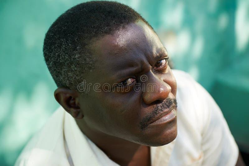 O retrato do meio envelheceu o homem africano que olha fixamente a câmera foto de stock