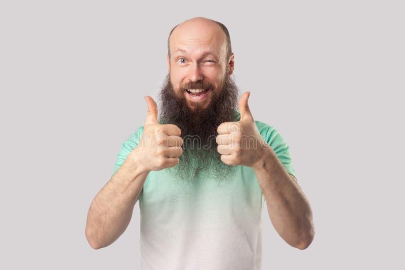 O retrato do meio satisfeito contente envelheceu o homem calvo com a barba longa na posição verde do t-shirt, nos polegares acima imagem de stock