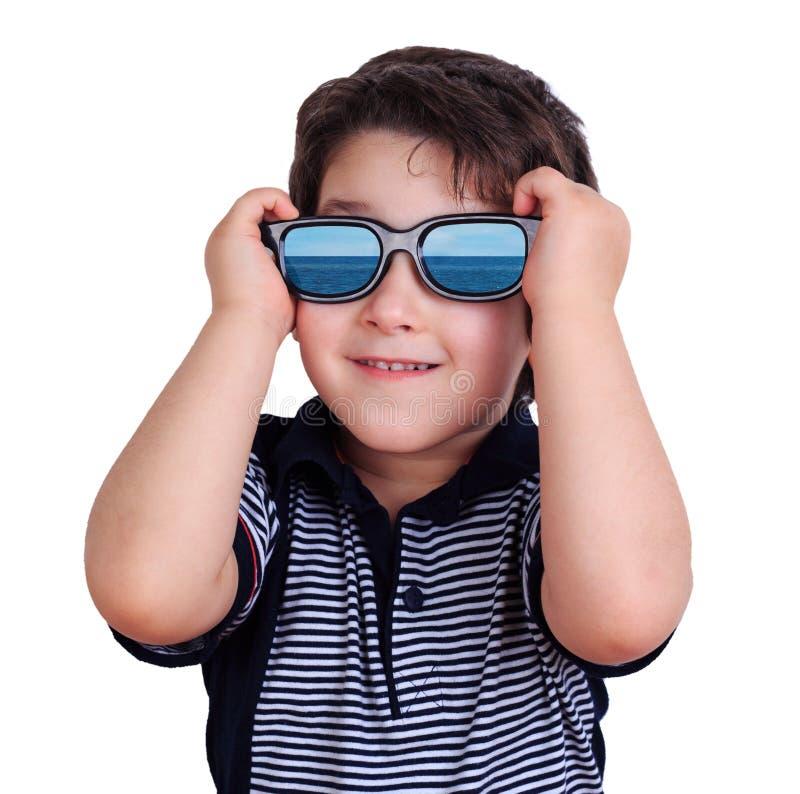 O retrato do menino bonito pequeno feliz nos óculos de sol com mar reflete imagens de stock