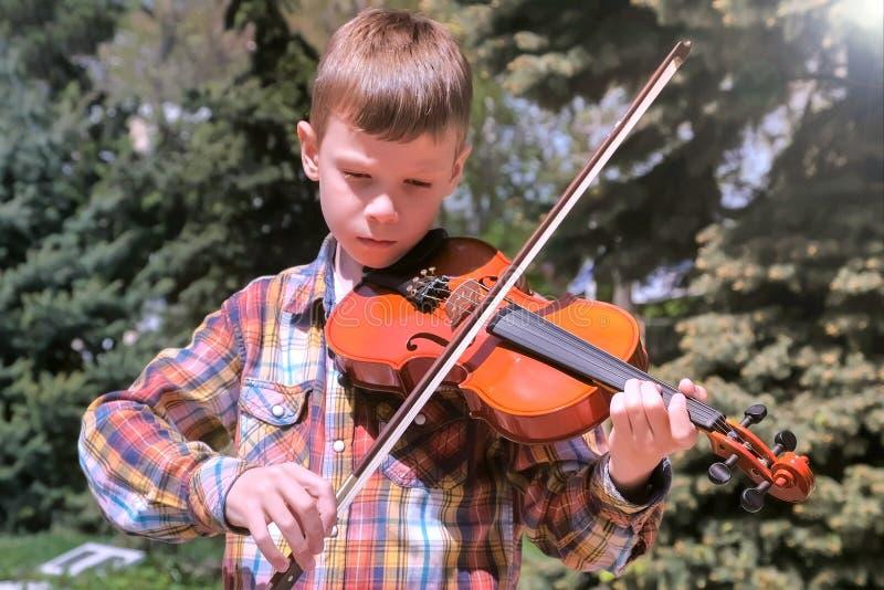 O retrato do menino da criança está jogando a posição do violino no parque imagem de stock royalty free