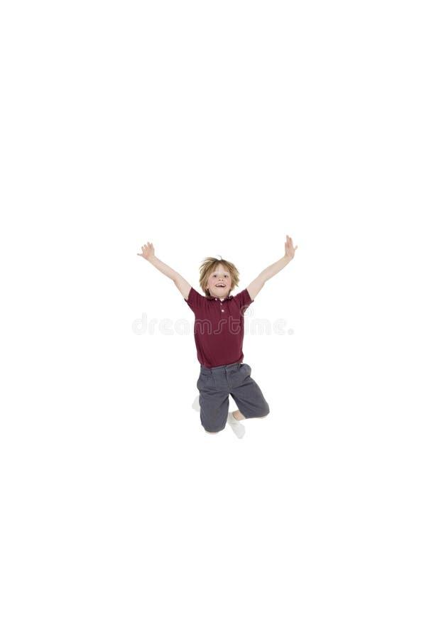 O retrato do menino elementar que salta no ar com braços aumentou sobre o fundo branco fotos de stock royalty free