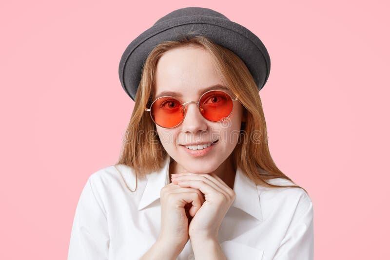 O retrato do modelo fêmea deleitado feliz em óculos de sol vermelhos redondos e no chapéu elegante, mantém as mãos sob o queixo,  fotografia de stock