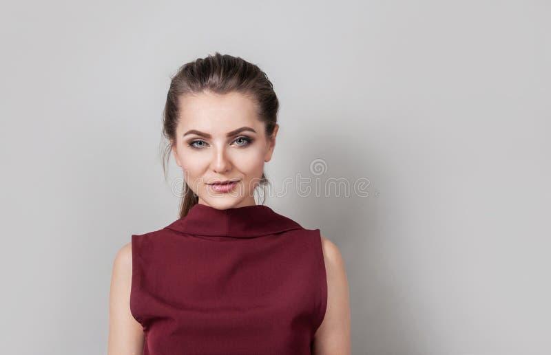 O retrato do negócio vestindo da jovem mulher bonita veste a vista da câmera com o sorriso, estando contra a parede cinzenta foto de stock