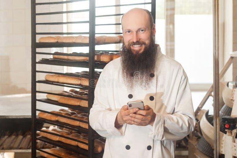 O retrato do padeiro adulto novo satisfeito do homem de negócios com a barba longa na posição uniforme branca na padaria e tem a  foto de stock