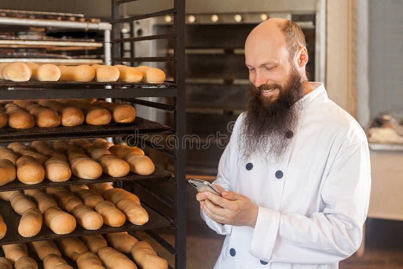O retrato do padeiro adulto novo satisfeito do homem de negócios com a barba longa na posição uniforme branca na padaria e tem a  fotografia de stock