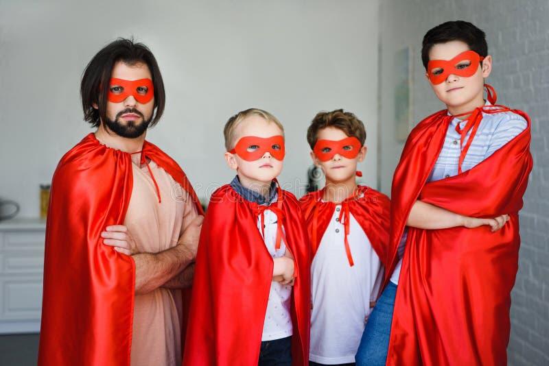 o retrato do pai e de filhos pequenos em trajes vermelhos do super-herói com braços cruzou-se imagem de stock royalty free