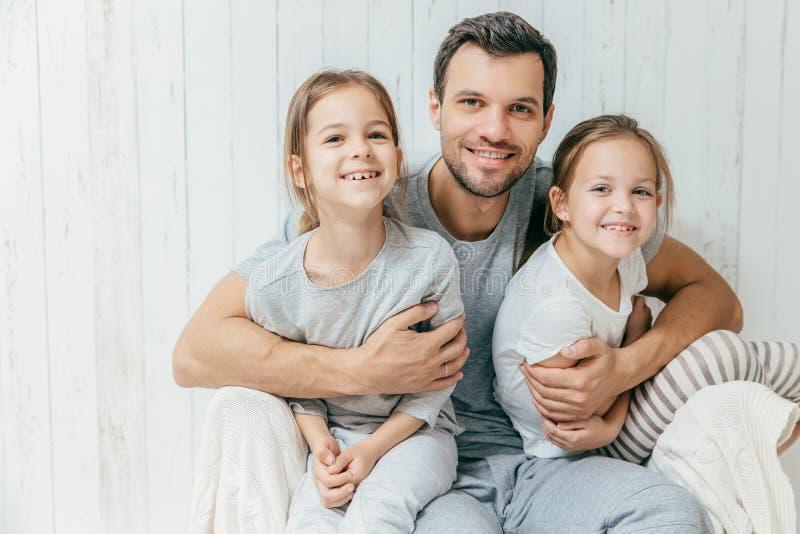 O retrato do pai novo feliz abraça suas duas filhas, amores foto de stock