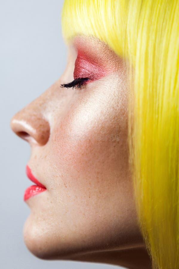 O retrato do perfil da opinião lateral da beleza do modelo fêmea novo bonito calmo com sardas, composição vermelha e peruca amare fotografia de stock royalty free