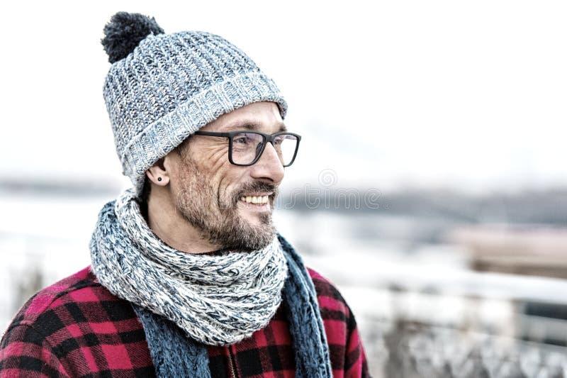 O retrato do perfil de sorriso novo do homem nos vidros e aquece a roupa feita malha para o homem de cidade fotografia de stock