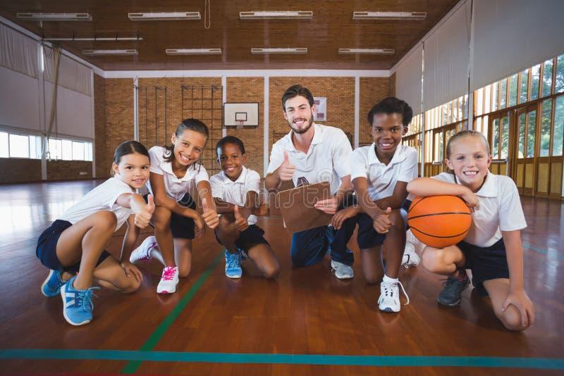 O retrato do professor e da escola dos esportes caçoa no campo de básquete fotografia de stock