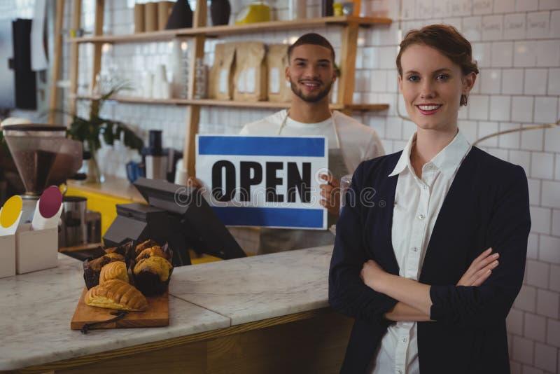 O retrato do proprietário seguro com a terra arrendada do garçom aberta assina dentro o café fotos de stock royalty free