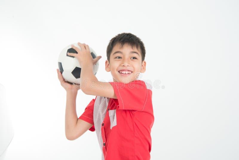 O retrato do rapaz pequeno toma uma bola do pé na mão no branco imagem de stock royalty free