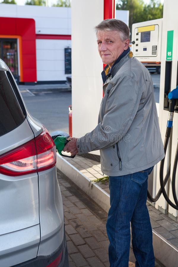 O retrato do reabastecimento maduro europeu do homem possui o carro no posto de gasolina no dia de verão foto de stock royalty free