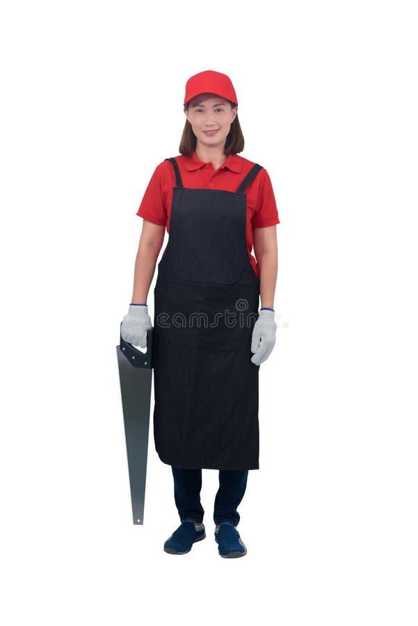 O retrato do trabalhador de jovem mulher que sorri no uniforme vermelho com avental, terra arrendada da mão da luva viu isolado n foto de stock royalty free