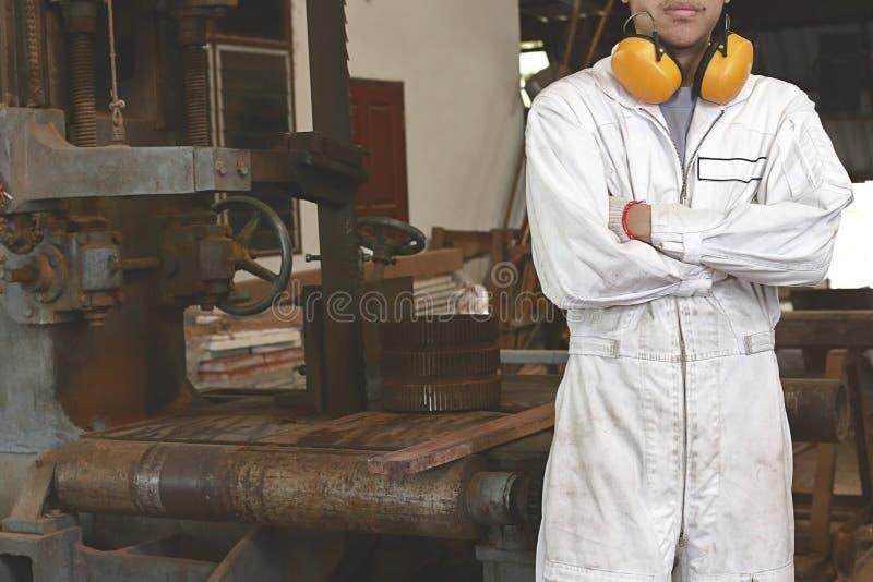 O retrato do trabalhador novo seguro na posição uniforme branca e cruza um os braços do ` s sobre a caixa com fundo da máquina da fotos de stock