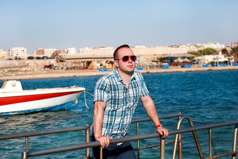 O retrato do turista e do viajante é de levantamento e andando no cais da praia, aprecia no sol e na ideia da paisagem do mar Hom imagens de stock