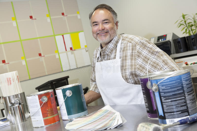 O retrato do vendas maduras felizes clerk no contador com as latas da pintura na loja de ferragens imagem de stock