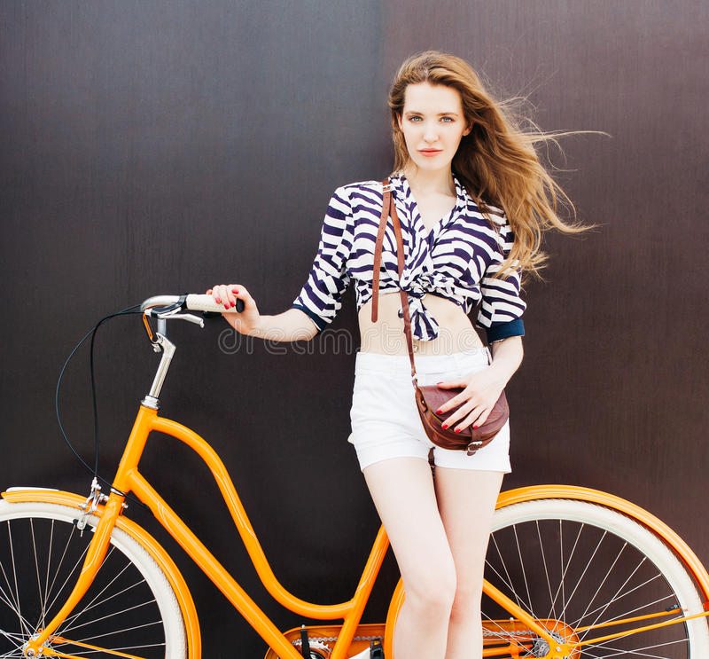 O retrato do verão da jovem mulher bonita está na bicicleta do vintage O vento funde seu cabelo Fundo escuro Cores mornas fotografia de stock royalty free