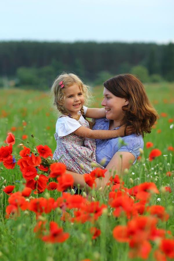 O retrato do verão da mãe de afago feliz e a filha nas papoilas colocam fotografia de stock