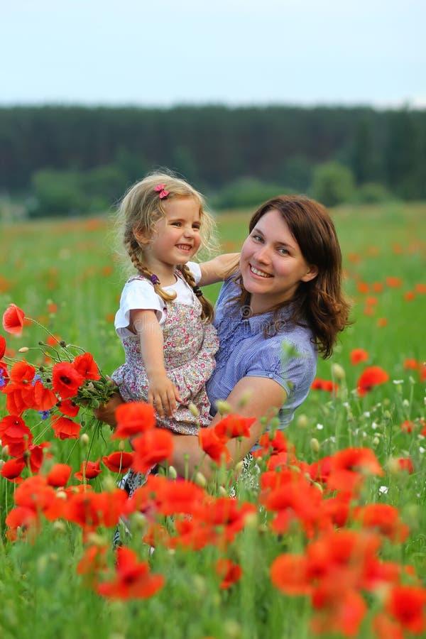O retrato do verão da mãe de afago feliz e a filha nas papoilas colocam imagens de stock