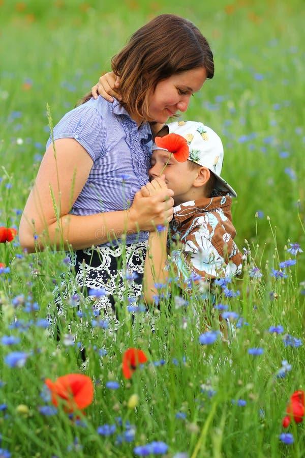 O retrato do verão da mãe de afago feliz e o filho nas papoilas de florescência colocam fotografia de stock royalty free
