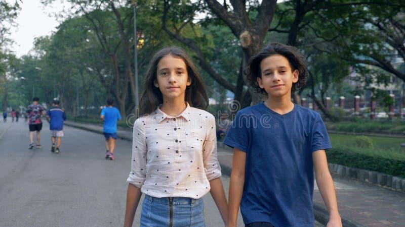 O retrato dos adolescentes, o menino e a menina que andam na natureza em um parque grande com os gêmeos do prazer, do irmão e da  imagens de stock