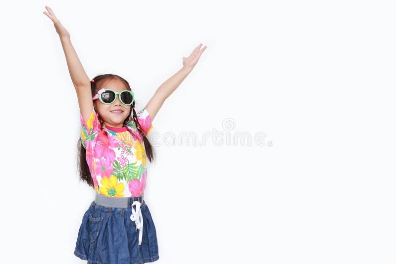 O retrato dos braços asiáticos pequenos felizes do estiramento da menina da criança abre largamente vestir um vestido floral e os imagem de stock