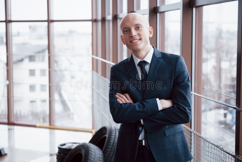 O retrato dos braços eretos de sorriso do homem de negócios novo cruzou a inclinação no armário no escritório imagem de stock royalty free