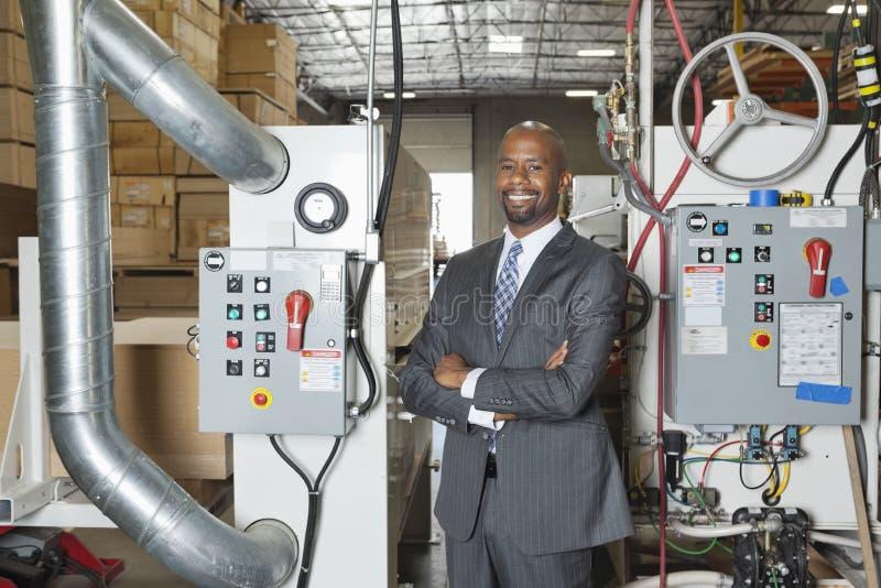 O retrato dos braços eretos do homem de negócios afro-americano cruzou-se com maquinaria no fundo foto de stock